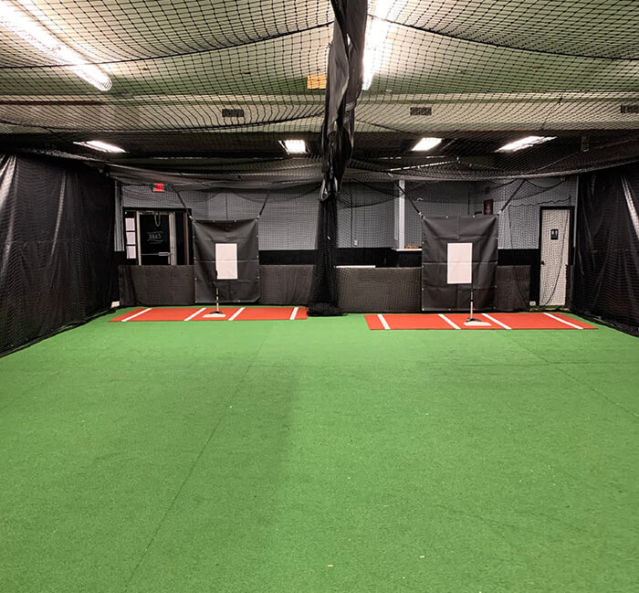 two batting cage tunnels with turf, tees and backstop