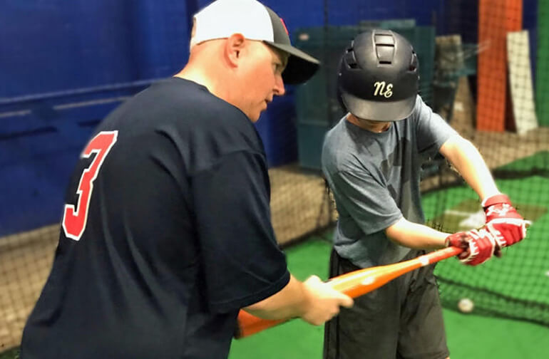 coach teaching player to hit