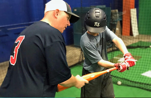 coach helping player swing the bat