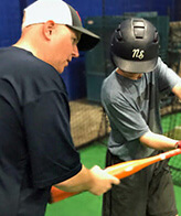 coach helping a young player with his swing